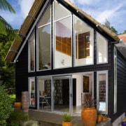 Previously, this home had minimal windows on its cottage, facade, home, house, real estate, siding, window