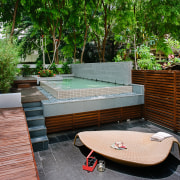 A view of this outdoor entertainment area featuring backyard, furniture, outdoor furniture, outdoor structure, patio, property, real estate, sunlounger, swimming pool, table, wood, yard, gray, green