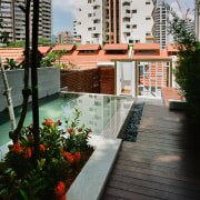 A view of this outdoor entertainment area featuring apartment, architecture, balcony, condominium, deck, house, outdoor structure, plant, real estate, reflection, residential area, walkway, water, black, gray