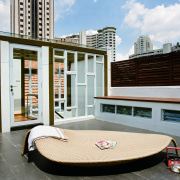 A view of this outdoor entertainment area featuring architecture, condominium, furniture, real estate, roof, gray, white