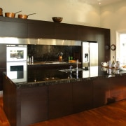 a view of this kitchen featuring bold dark cabinetry, countertop, cuisine classique, interior design, kitchen, room, brown