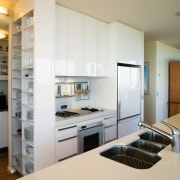 The relatively compact kitchen features a number of cabinetry, countertop, home appliance, interior design, kitchen, gray, white
