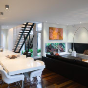 The open stairway adds a strong graphic element ceiling, interior design, living room, room, table, gray