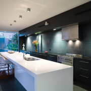 The gallery-style kitchen, which continues the strong horizontal architecture, countertop, house, interior design, kitchen, property, real estate, gray, black