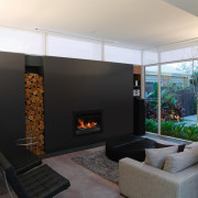 A second living area, which doubles as a fireplace, hearth, interior design, living room, wood burning stove, black, white