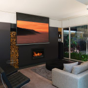 A second living area, which doubles as a fireplace, hearth, interior design, living room, wall, black, white