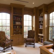 An oak-panelled study features arched windows with simple bookcase, cabinetry, ceiling, estate, furniture, hardwood, home, interior design, library, living room, real estate, shelving, window, brown