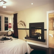 A view of the master bedroom featuring bed, bedroom, ceiling, fireplace, hearth, home, interior design, living room, room, orange