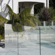 A view of this outdoor pool area featuring architecture, arecales, glass, house, outdoor structure, palm tree, gray