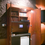 A cabinets hide a wall mounted touchpad fof cabinetry, furniture, interior design, room, wood, brown