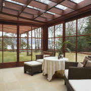 A view of the conservatory featuring dark stained daylighting, estate, house, interior design, outdoor structure, porch, property, real estate, roof, window, red