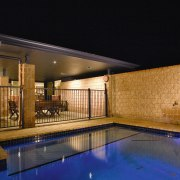 This outdoor living area features clyde stone bricks architecture, estate, home, house, landscape lighting, lighting, property, real estate, reflection, residential area, swimming pool, black