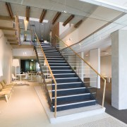 A view of the staircase featuring glass balustrading architecture, ceiling, daylighting, handrail, interior design, lobby, real estate, stairs, gray