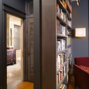 A view of the library which gives access bookcase, cabinetry, floor, flooring, furniture, interior design, library, shelf, shelving, brown