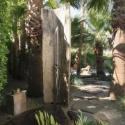 The outdoor shower is under a palm tree. arecales, backyard, courtyard, garden, hacienda, landscape, landscaping, outdoor structure, palm tree, plant, property, real estate, tree, yard