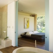 A view of the bathroom featuring oval limestone architecture, bathroom, ceiling, daylighting, door, estate, floor, flooring, home, house, interior design, real estate, room, suite, wall, window, wood, wood flooring, white, brown
