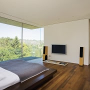 A view of this master bedroom featuring brazilian architecture, bedroom, ceiling, estate, floor, hardwood, house, interior design, living room, property, real estate, room, window, wood, wood flooring, gray