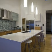The open-plan kitchen uses a variety of materials, architecture, countertop, floor, flooring, interior design, kitchen, real estate, room, wood flooring, gray