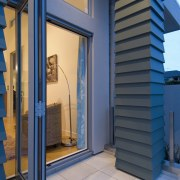 Large bifold doors lead from the open-plan living architecture, facade, home, structure, blue, gray