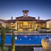 With its fusion of Spanish and Italian design estate, evening, hacienda, home, house, leisure, lighting, mansion, property, real estate, reflection, residential area, resort, sky, swimming pool, villa, water, blue