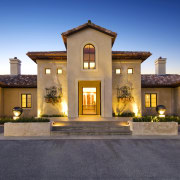 A snse of symmetry defines the front entrance. building, elevation, estate, facade, home, house, landscape lighting, lighting, mansion, property, real estate, residential area, sky
