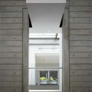 A concrete projection draws attention to an opening architecture, daylighting, door, facade, home, house, window, gray