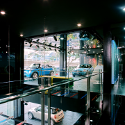 Cars are displayed on raw concrete floors tinted glass, interior design, black
