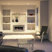 A view of a fireplace from Escea. - floor, flooring, furniture, home, interior design, living room, room, shelving, wall, orange