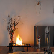 A view of a fireplace from Real Fires. ceiling, fireplace, hearth, heat, home, interior design, lamp, light fixture, lighting, lighting accessory, still life photography, table, wood, gray, black