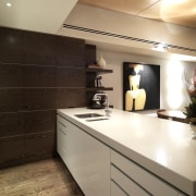 View of kitchen designed by Nicholas Murray featuring cabinetry, ceiling, countertop, cuisine classique, floor, interior design, kitchen, room, sink, under cabinet lighting, brown