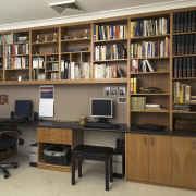 A view of a storage space by Creative bookcase, cabinetry, desk, furniture, institution, library, library science, office, public library, shelf, shelving, brown, black, gray