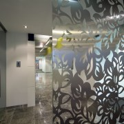 A glass screen with a delicate leaf pattern ceiling, glass, interior design, lobby, mural, wall, gray, black