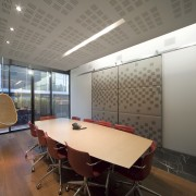 The cubic pattern on the fabric panels in architecture, ceiling, conference hall, daylighting, interior design, office, real estate, table, gray