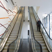 interior view of building featuring escalators, lighting, doors architecture, escalator, line, metropolitan area, stairs, structure, gray