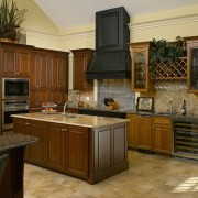 A simple door style and stacked appliances complement cabinetry, countertop, cuisine classique, hardwood, interior design, kitchen, room, brown, orange