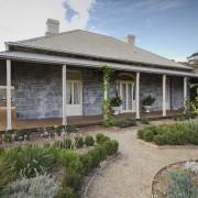 The restored jarrah verandah and bluestone walls replicate backyard, cottage, estate, facade, farmhouse, home, house, outdoor structure, property, real estate, villa, yard, gray