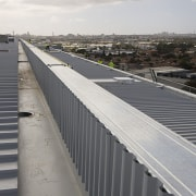 The building's roof was supplied and installed by asphalt, bridge, daylighting, fixed link, guard rail, infrastructure, line, metropolitan area, road, road surface, roof, sky, structure, walkway, gray