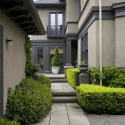 Exterior view of century old house featuring landscaping, architecture, courtyard, estate, facade, garden, grass, home, house, landscaping, mansion, neighbourhood, plant, property, real estate, residential area, walkway, window, yard, gray, black