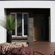 The use of smiliar materials both outside and architecture, building, door, facade, home, house, real estate, residential area, siding, window, black