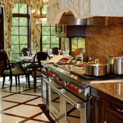 A large Wolf range with a faux stone countertop, flooring, interior design, kitchen, room, brown