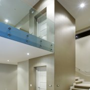 The stairs wrap around a central lift core, architecture, ceiling, daylighting, floor, glass, handrail, house, interior design, lighting, real estate, stairs, wall, gray