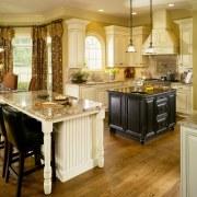 View of kitchen which features kitchen island with cabinetry, countertop, cuisine classique, floor, flooring, hardwood, interior design, kitchen, room, wood flooring, orange, brown