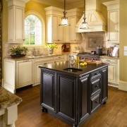View of kitchen which features kitchen island with cabinetry, countertop, cuisine classique, floor, flooring, hardwood, interior design, kitchen, laminate flooring, room, wood flooring, orange, brown