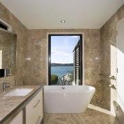 View of the master bathroom with floor-to-ceiling marble, bathroom, ceiling, countertop, estate, floor, flooring, home, interior design, real estate, room, sink, tile, wood flooring, gray, brown