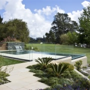 View of pool area with clear glazed walls, backyard, estate, garden, grass, landscape, landscaping, lawn, leisure, outdoor structure, pond, property, real estate, reflecting pool, swimming pool, water, water feature, yard, brown, white