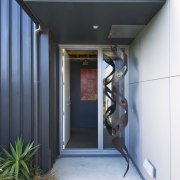 Exterior view of entrance way featuring landscaping, glazing, architecture, door, home, house, real estate, black, white