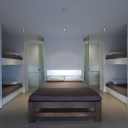 View of a bunkroom with bathroom featuring bunkbeds, architecture, bed frame, furniture, hostel, interior design, room, gray