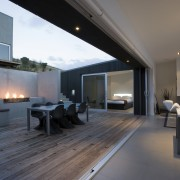 View of the central courtyard which features decking, architecture, floor, flooring, house, interior design, living room, real estate, window, wood flooring, gray, black