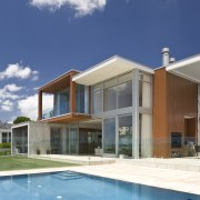 Exterior view of home and pool with framelss architecture, elevation, estate, facade, home, house, property, real estate, residential area, sky, swimming pool, villa, window, white
