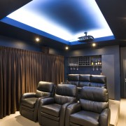 View of a home theatre with screen, projector, ceiling, interior design, lighting, black